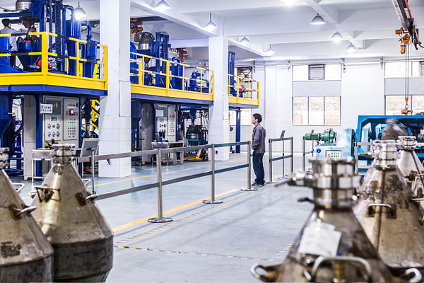 Worker observing magnet manufacturing machines